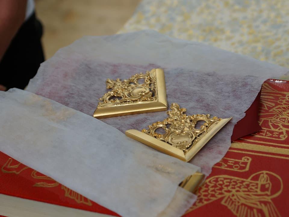 Zwei goldene kunstvoll gestaltete Buchecken auf Seidenpapier.