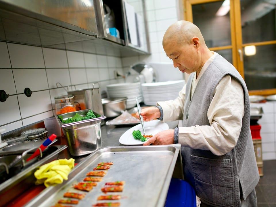 Frau steht in Küche und legt Essen auf Tellern