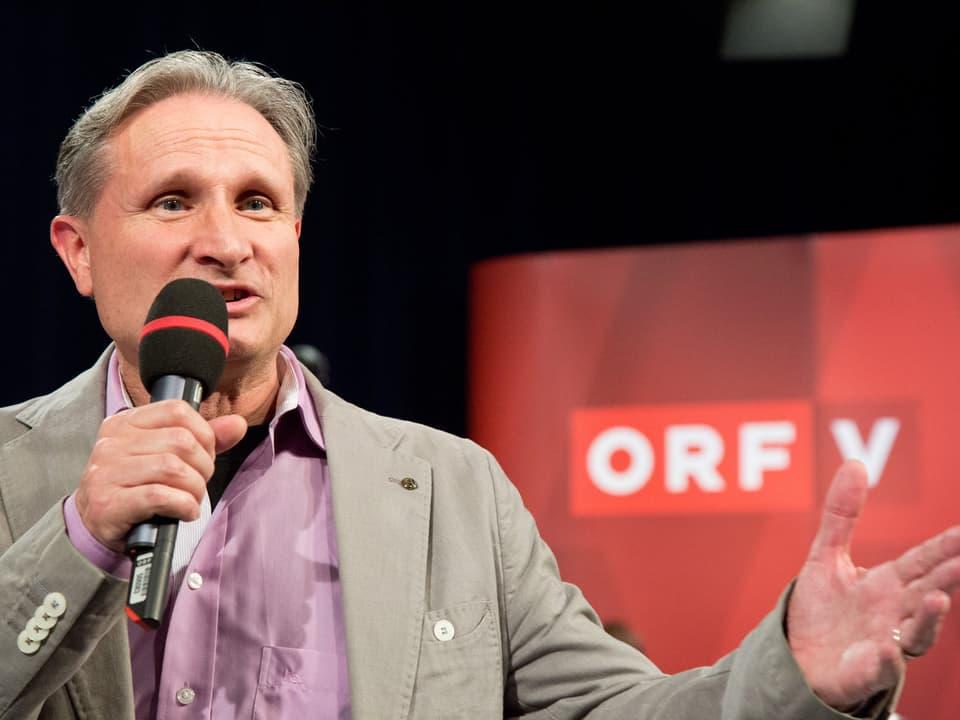 Der Moderator mit Mikrofon bei der Begrüssung.