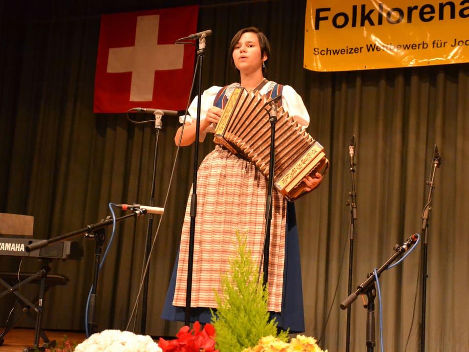 Die junge Jodlerin trägt eine Tracht und begleitet sich während ihres Auftritts auf dem Schwyzerörgeli.