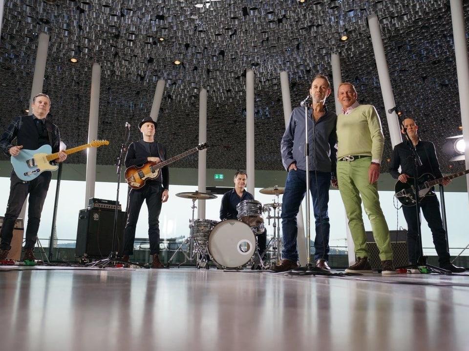 Die Musiker von Züri West sind in einem Saal mit spiegelndem Boden an ihren Instrumenten. Kurt Aeschbacher steht neben Kuno Lauener beim Standmikrofon.