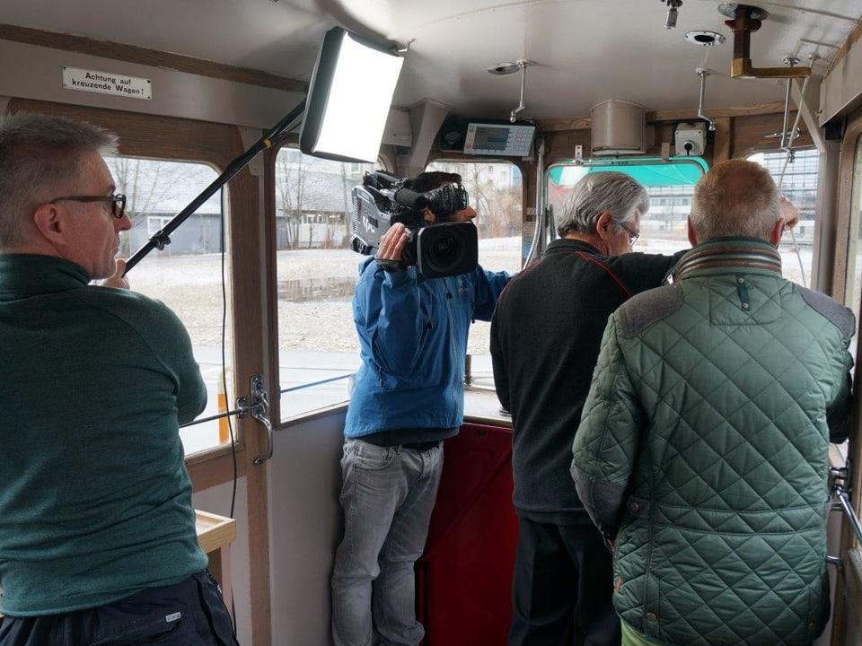 Im Führerstand des ältesten Tram der Stadt Bern hält der Beleuchter seine Lampe, damit Roland Seiler gut ausgeleuchtet ist. Kurt Aeschbacher ist von hinten zu sehen, ebenso der Kameramann.
