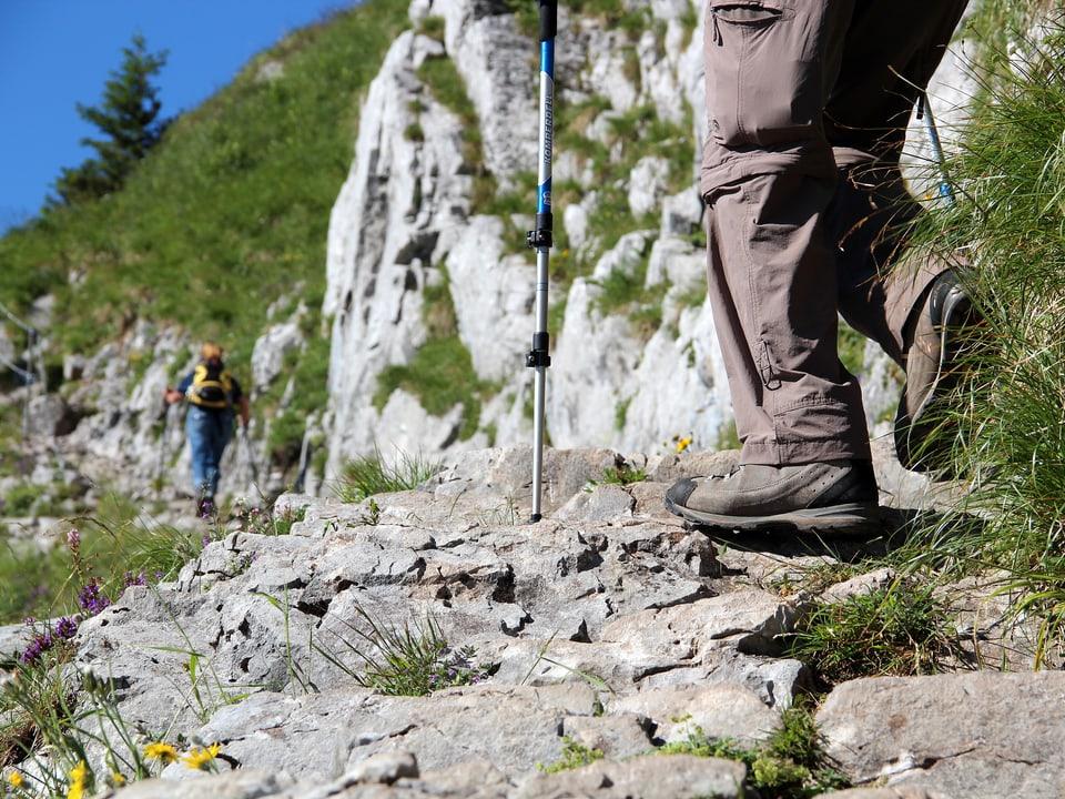 Wanderer auf steilem Bergweg.