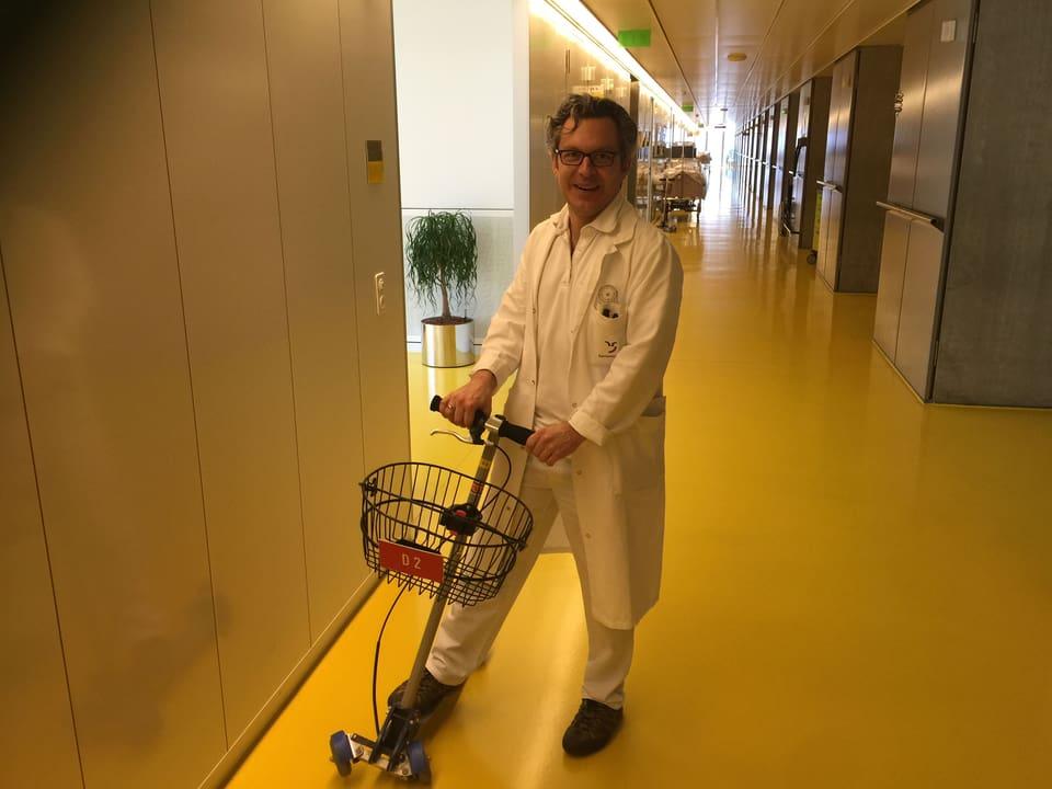 Arzt mit Roller im Spitalgang.
