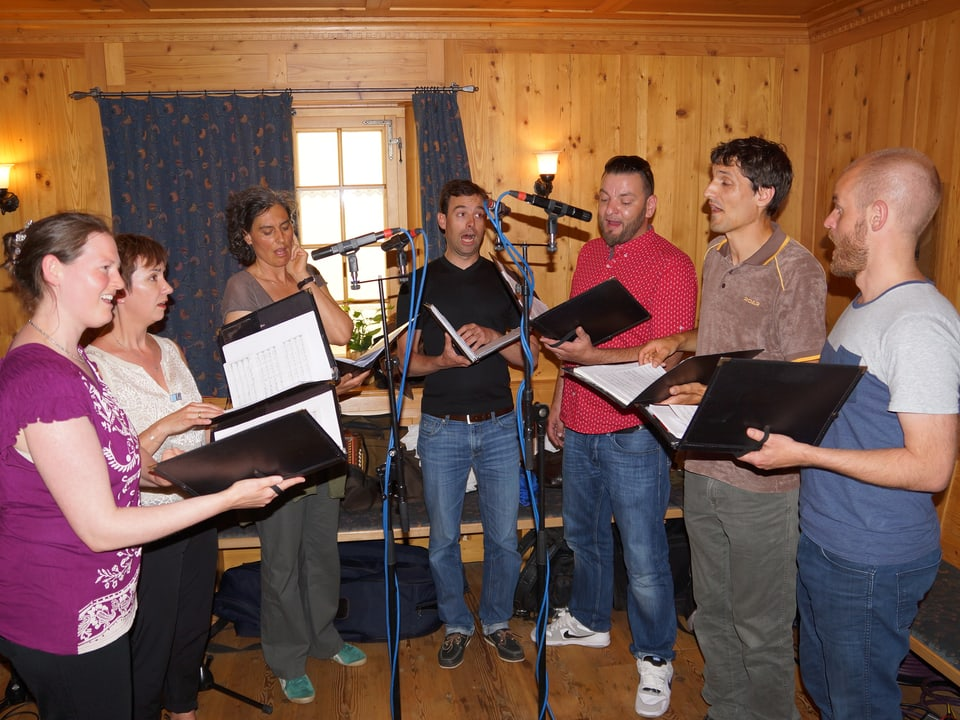 Die Sängerinnen und Sänger stehen mit ihren Notenblättern im Halbkreis.