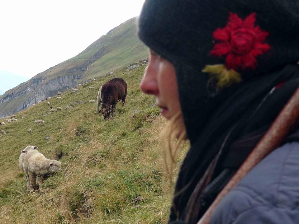 Herdenschutz: Ein guter Herdenschutz auf der Alp beginnt mit professioneller Behirtung. (Grossaufnahme einer Hirtin, Schafe weiden im Hintergrund)