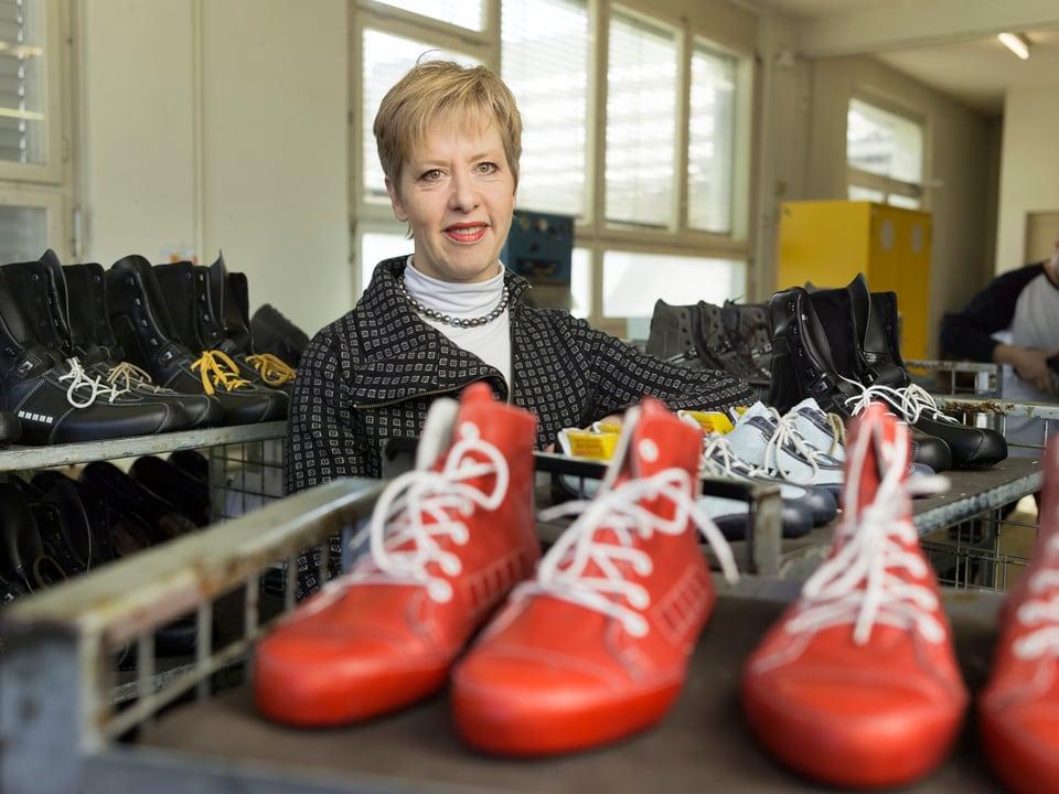 Barbara Artmann in der Fabrik, von Schuhen umgeben.
