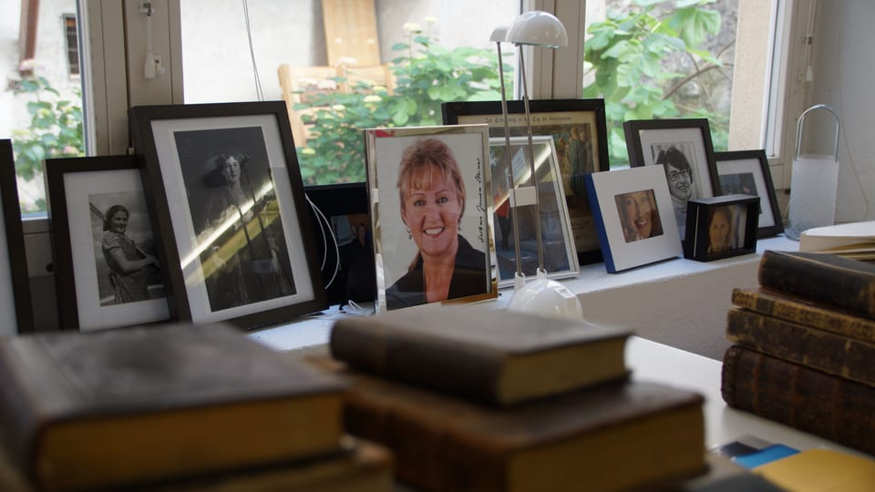 Banc da fanestra cun diversas fotografias enramadas, tranter auter da Barbara Janom Steiner e Silva Semadeni.