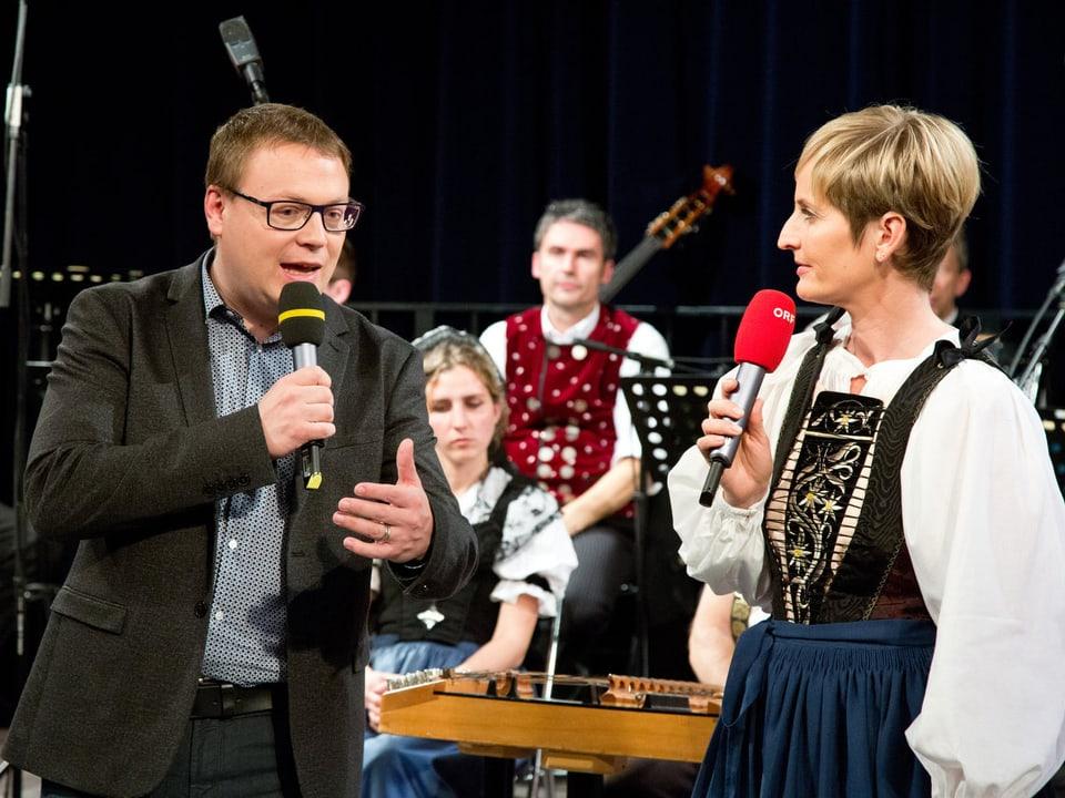 Moderator und Moderatorin unterhalten sich auf der Bühne, hinter ihnen sitzen Musikantinnen und Musikanten einer Volksmusikformation.