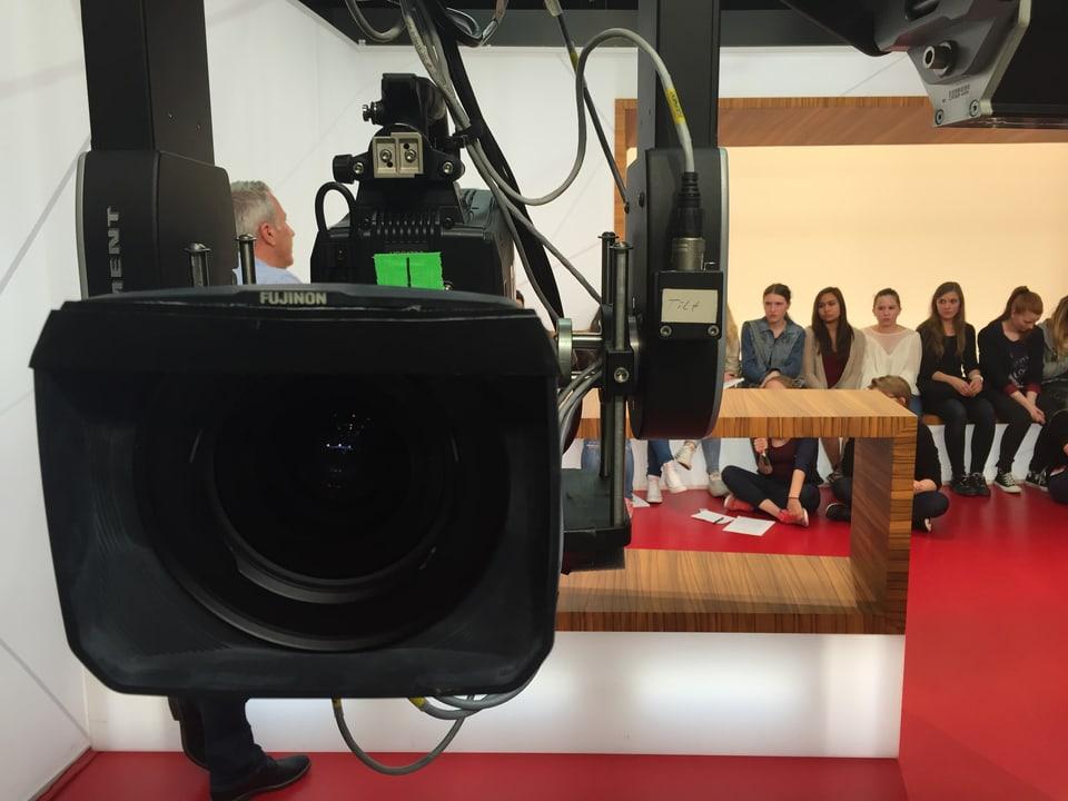 Kameralinse, im Hintergrund Schüler.