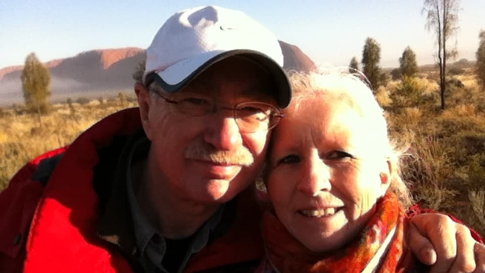 Erich und Monica Rubitschung posieren in den Ferien in Australien vor einer Graslandschaft.