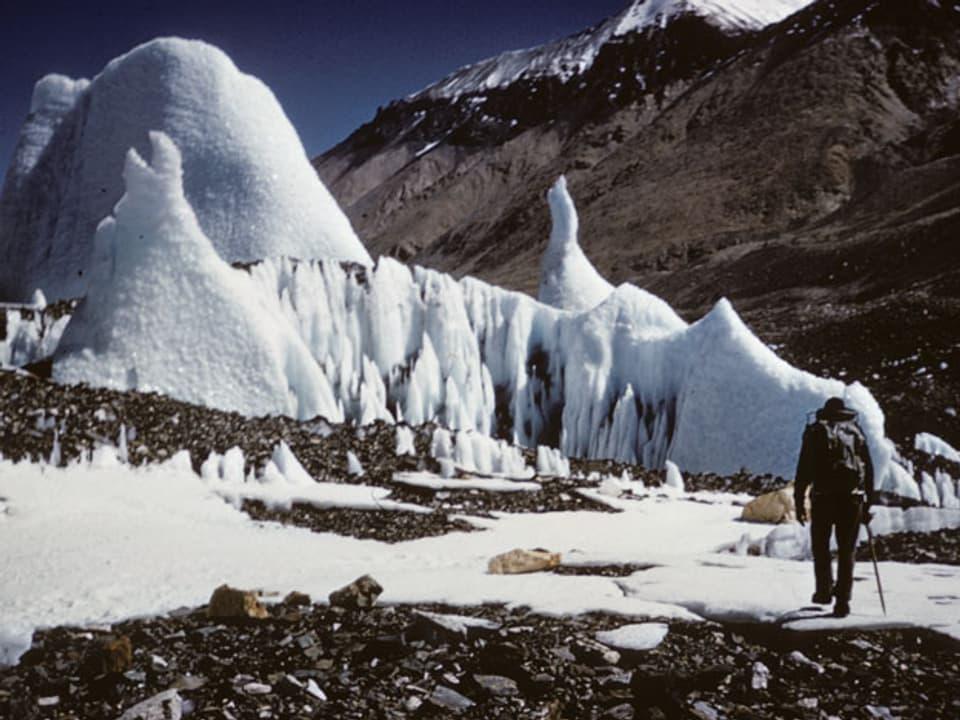 Mann läuft durch Schnee- und Steinlandschaft.
