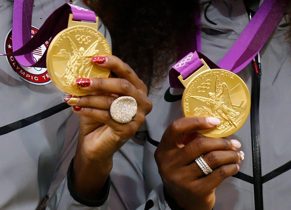 Die beiden Williams-Schwestern halten je eine Goldmedallie in der Hand. Im Bildausschnitt ist je eine Hand mit Medallie zu sehen. Beide haben auffällige Nägel: Rot-goldene und rosarote.