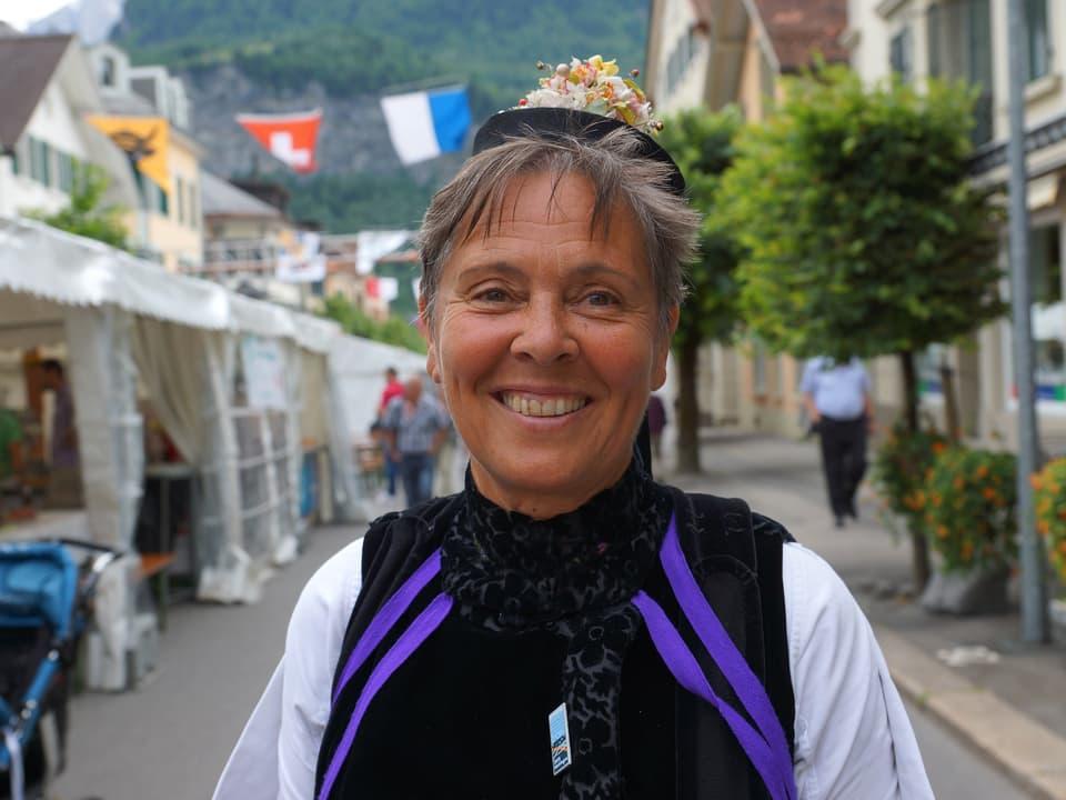 Die Trachtenfrau steht in einer mit Fahnen geschmückten Strasse in Meiringen.