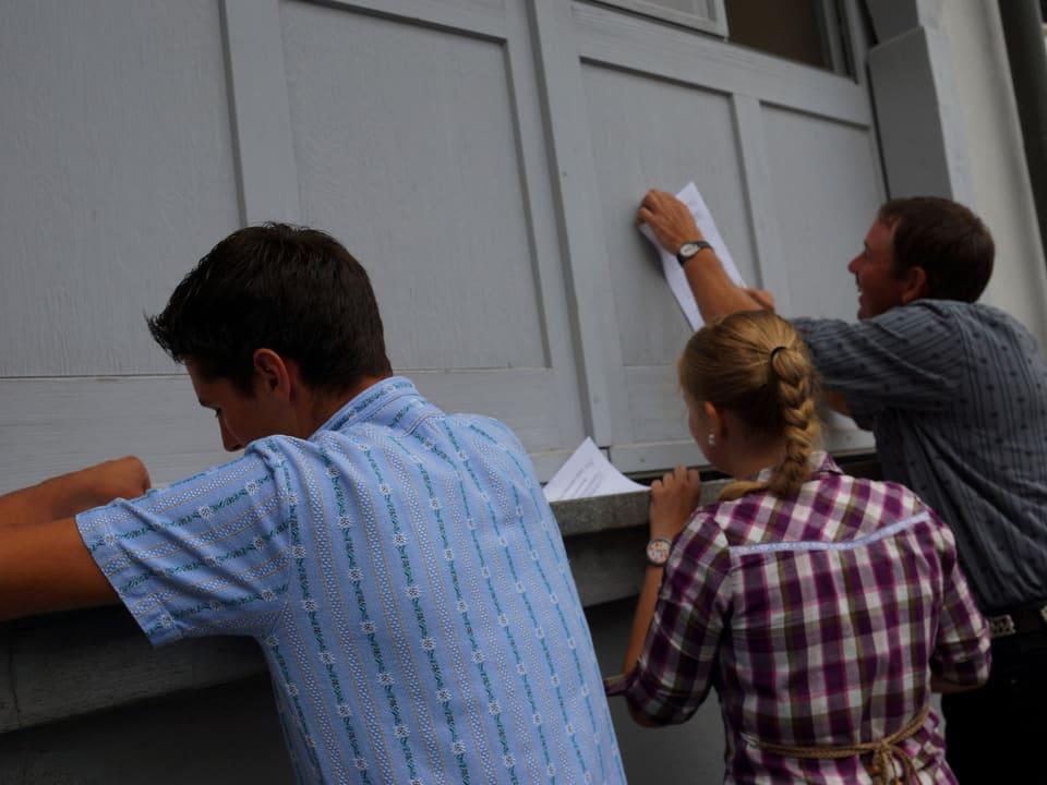 Zwei Männer und eine junge Frau schreiben mit der Wand als Unterlage auf ein Blatt Papier.