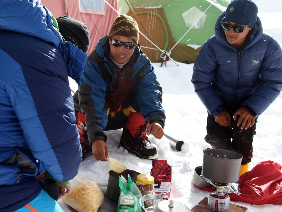 Sherpas sitzen im Schnee vor einem kleinen Kocher und einer Auslage mit verschiedenen Nahrungsmitteln.