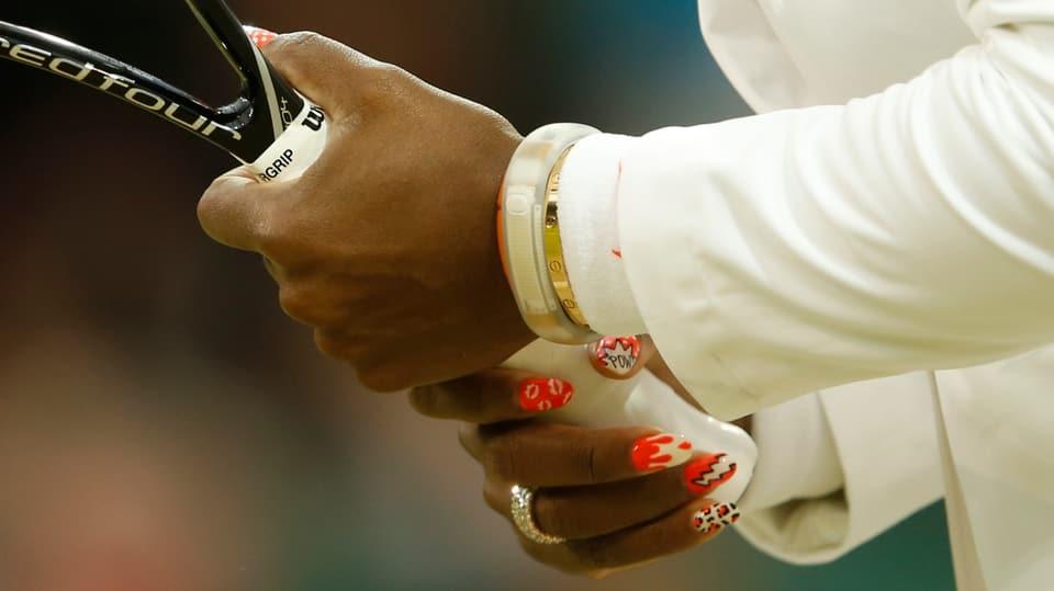 Serena Williams Hände halten ihr Racket. Ihre Nägel sind sehr auffällig lackiert: Jeder Nagel hat ein anderes Muster mit den Farben orange, weiss und schwarz.