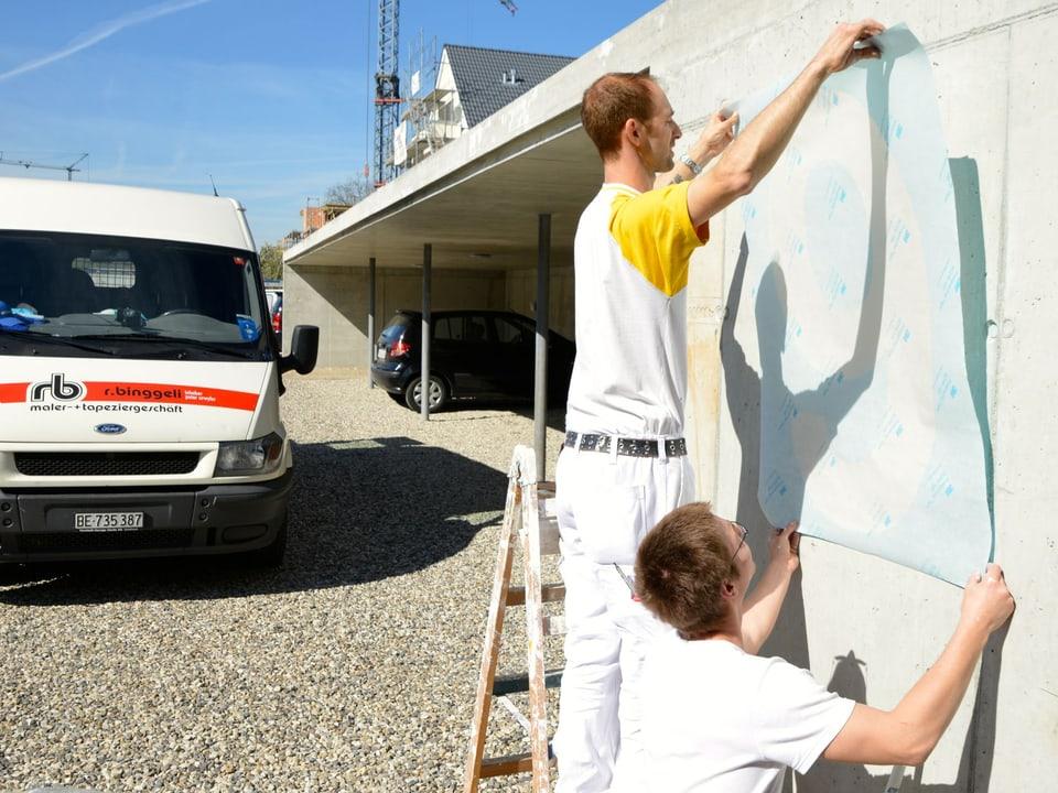 Zwei Maler kleben eine Folie an die Mauer.