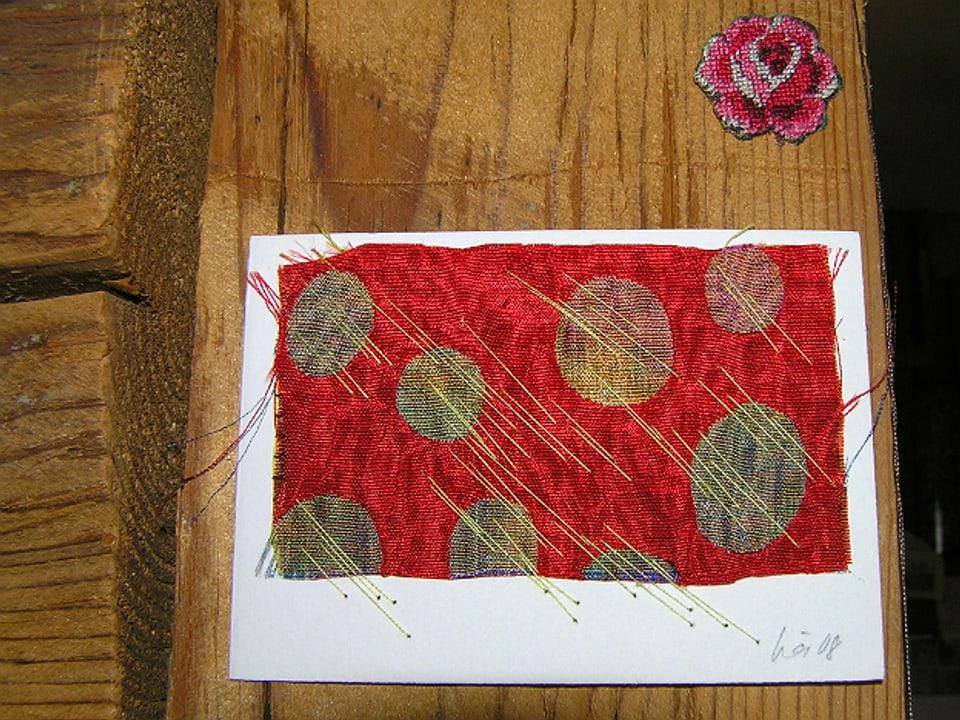 Holzwand mit einem gestickten Bild und einer ausgeschnittenen kleinen Rose in Kreuzstich. Das Bild besteht aus einem rotglänzenden Stoff mit grossen olivgoldenen Punkten und darüber gestickten, diagonal gruppierten gelbgoldenen langen Fäden.