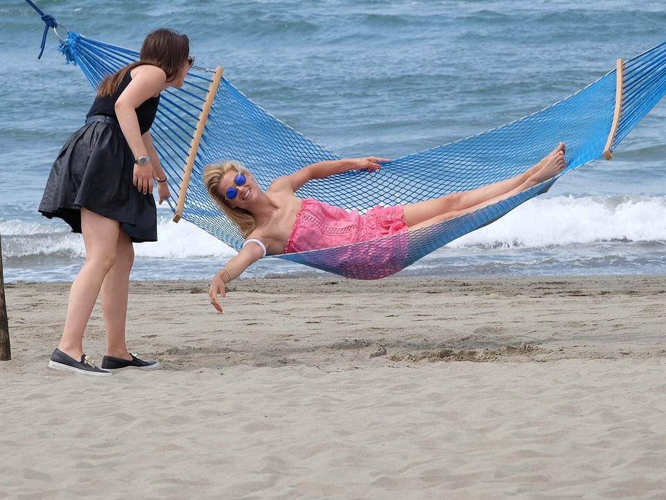 Michelle Hunziker liegt am Strand in einer Hängematte. Tochter Aurora schaukelt Michelle Hunziker hin und her.