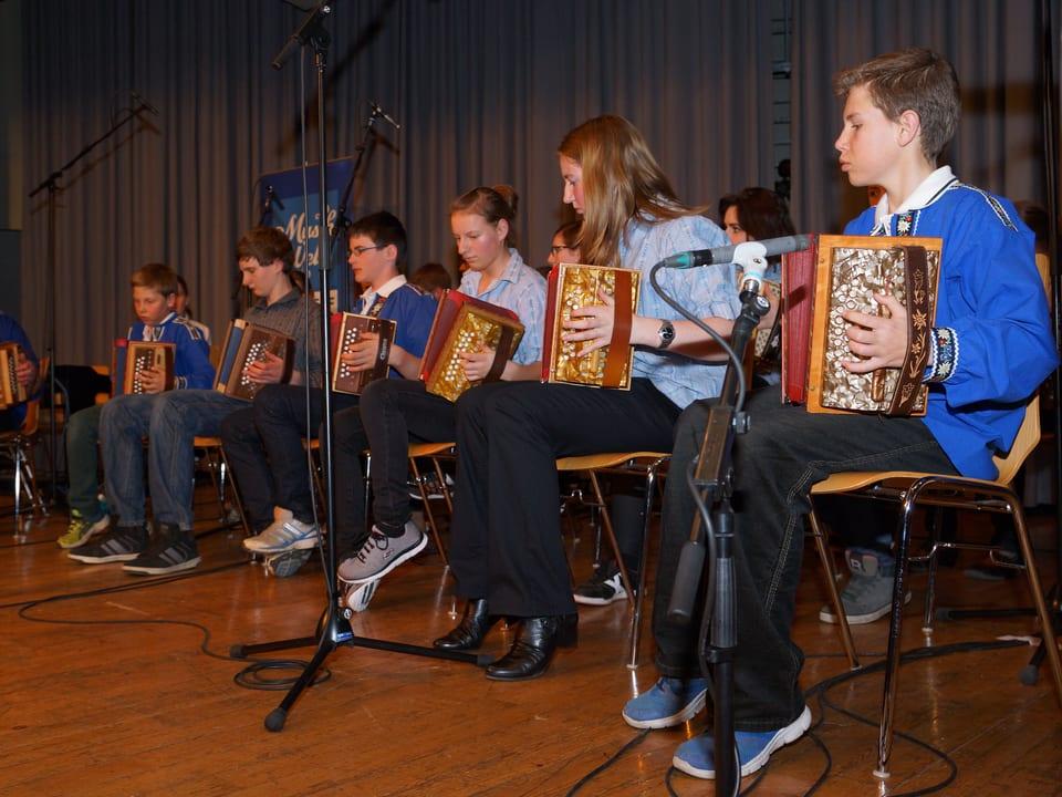 Die Jugendlichen sitzen alle in einer Reihe auf Stuhl auf der Bühne.
