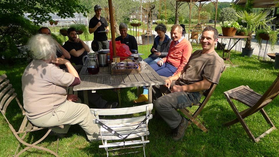 Familie Linder sitzt mit dem Fernsehteam im Grünen auf Holzstühlen an einem Tisch im Schatten und beendet soeben den z'Vieri.