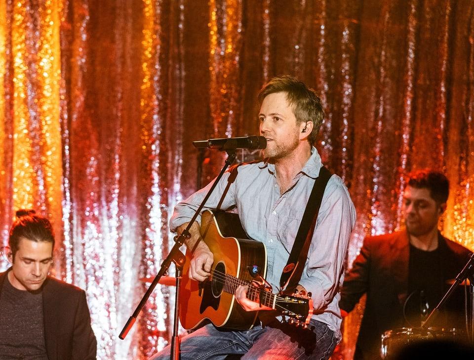 Ein sitzender Mann mit Mikrofon spielt Gitarre und singt.