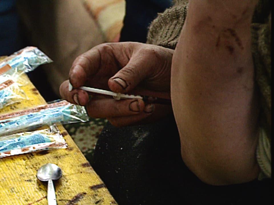 Hand eines Junkies, der sich Heroin spritzt.