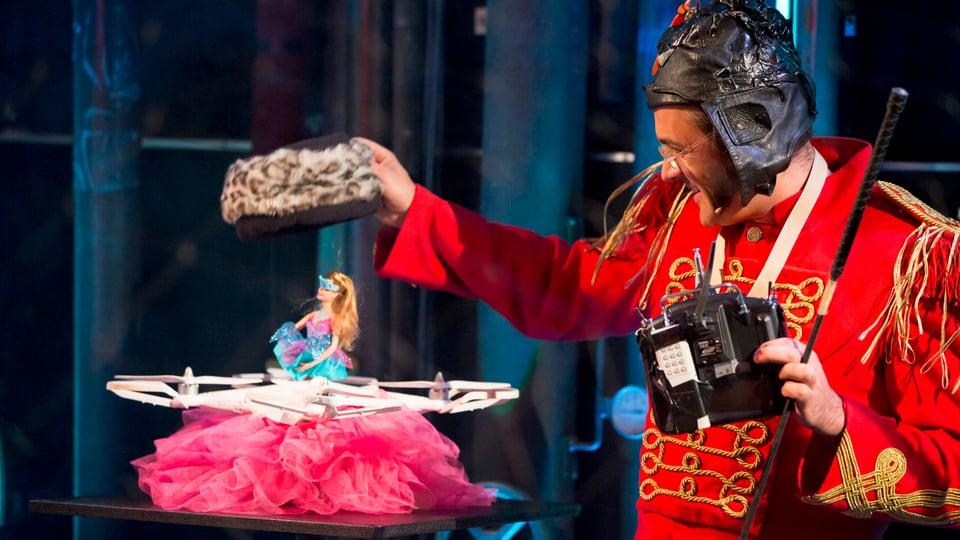 Superbuffo mit rotem Zirkusgewand und schwarzem Helm setzt seiner Barbiepuppe einen Hut auf.