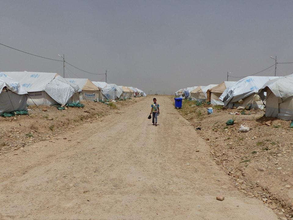 Ein Junge läuft alleine auf einem Weg durch das Flüchtlingscamp.