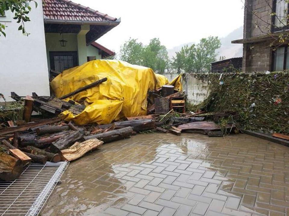Schutt und angeschwemmtes Holz vor einem Haus.