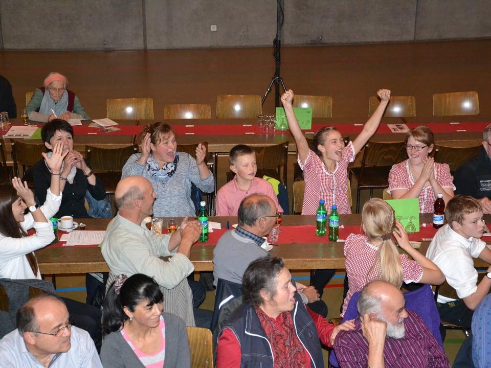 Mitten in den Zuschauern streckt eine junge Musikantin ihre Hände freudig in die Höhe.