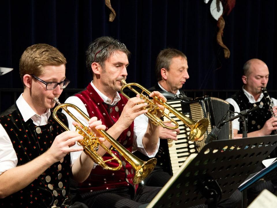 Zwei Trompetenspieler, ein Akkordeonist und ein Klarinettist beim Musizieren.