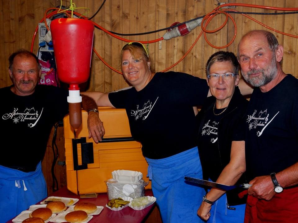 Drei Männer und eine Frau in blauen Küchenschürzen beim Hamburger-Stand.