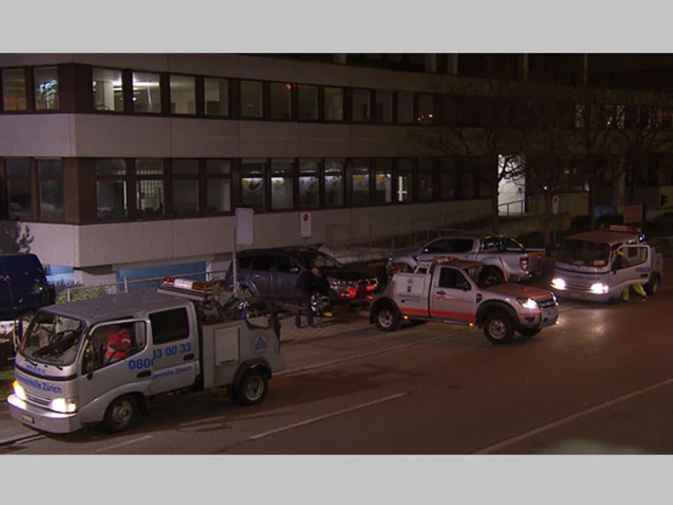 Drei Abschleppwagen schleppen Autos auf einem Parkplatz ab.