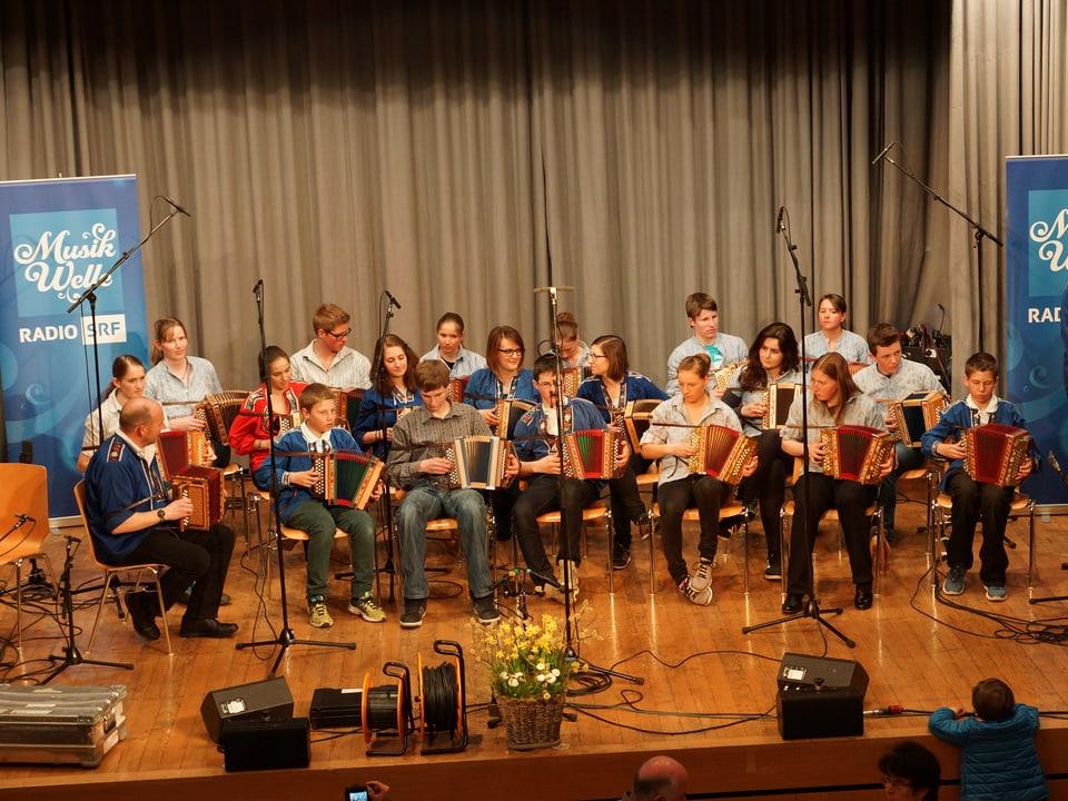 Ca. 20 jugendliche Akkordeonisten sitzen auf der Bühne.