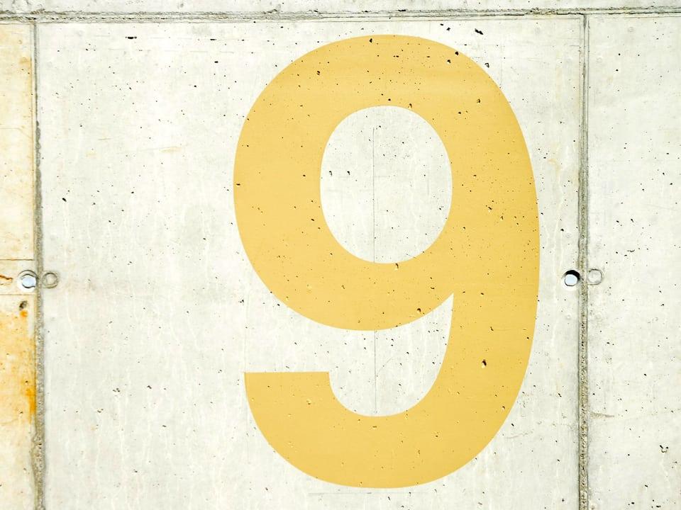 Gelbe Nummer 9 auf einer Betonwand.