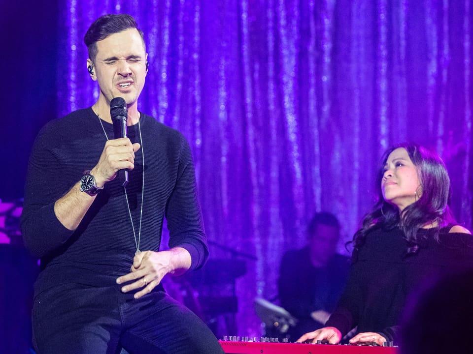 Ein Mann singt während ihn eine Frau auf einem Keyboard begleitet.