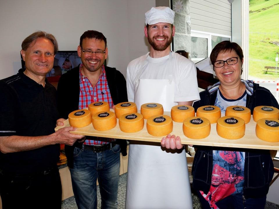 Der Käsermeister präsentiert seinen Besuchern mehrere kleine Käselaibe auf einem langen Brett.