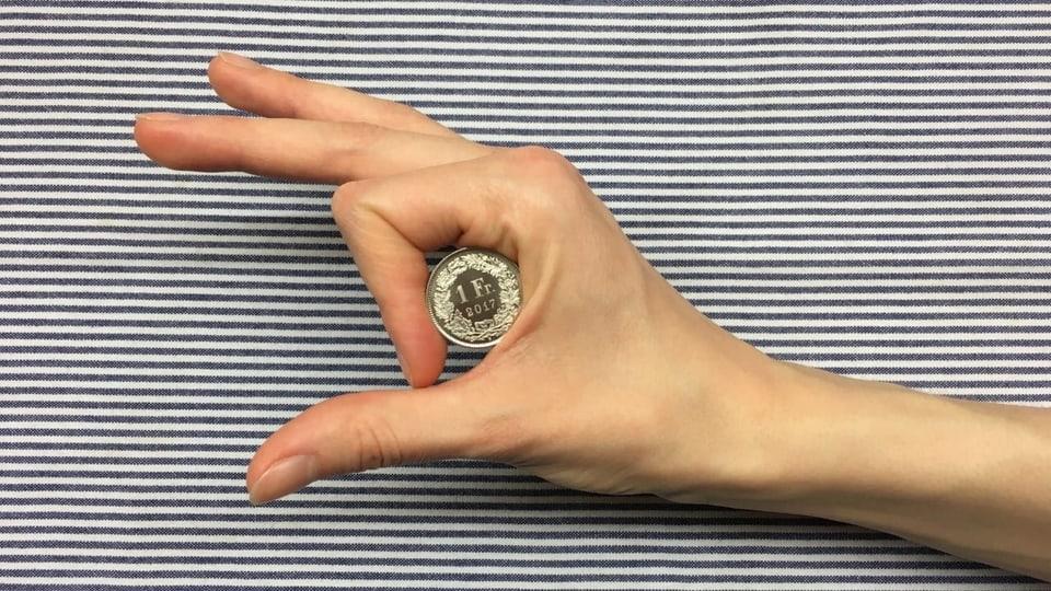 Hand hält Einfränkler zwischen Daumen und Zeigefinger