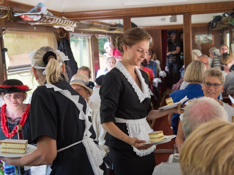 Eine junge Frau in Serviertocher-Kleidung bringt Cremeschnitten an einen Tisch