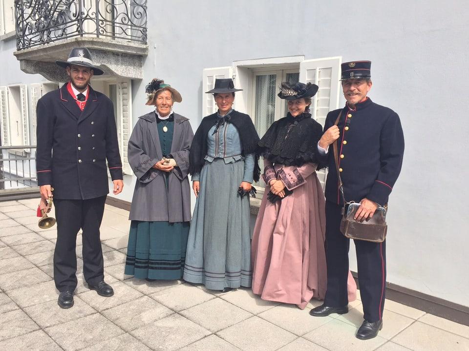 Zwei Herren und drei Damen in historischen Kostümen vor einer Hausmauer