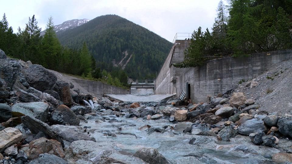 Eine Kraftwerkstaumauer mit wenig Restwasser im Fluss darunter.