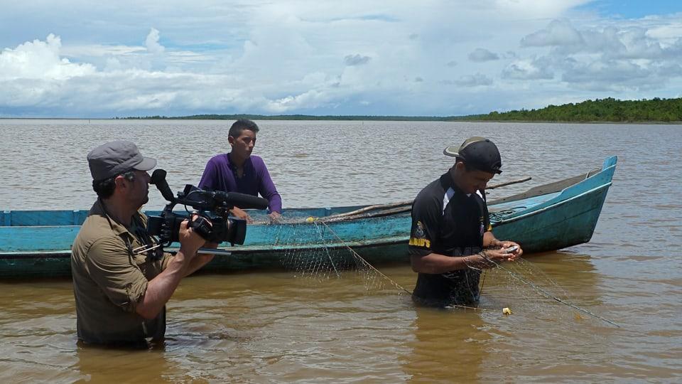 Kameramann Laurent Stoop steht hüfttief im Wasser und filmt zwei Fischer im Amazonasdelta.