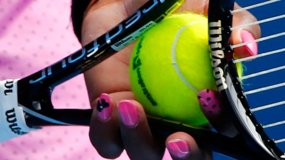 Serena Williams hält Tennisball und ihr Racket in der Hand. Ihre pinken Nägel passen zu ihrem pinkenen Top, das man im Hintergrund erkennen kann.