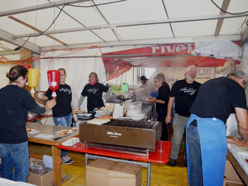 Blick in die Küche vom Festzelt mit Männern und Frauen, die fleissig anpacken.