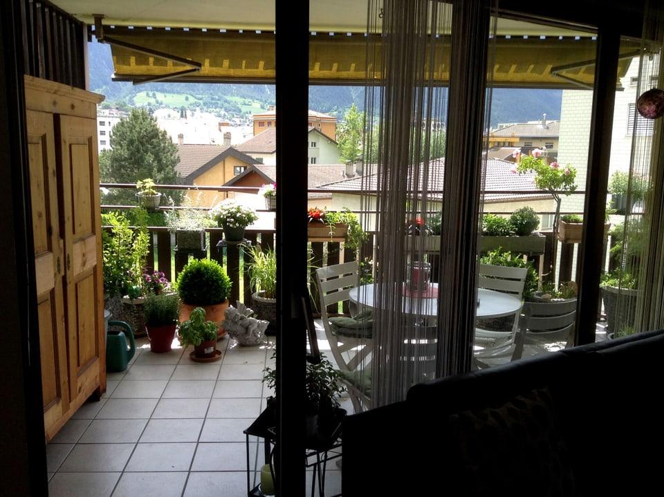 Blick auf einen Balkon mit Plattenboden. An der linken Wand steht ein Holzschrank und der Mitte ein runder Tisch mit Stühlen.