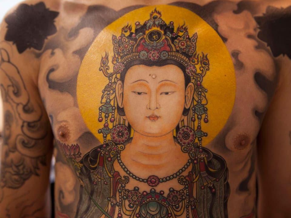 Tätowierte Gottheit auf der Brust eines Mannes.
