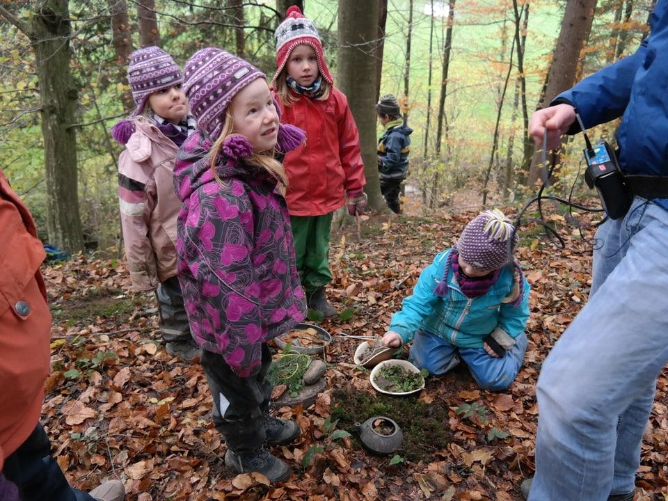 Kinder in ihrem Restaurant im Waldkindergarten.