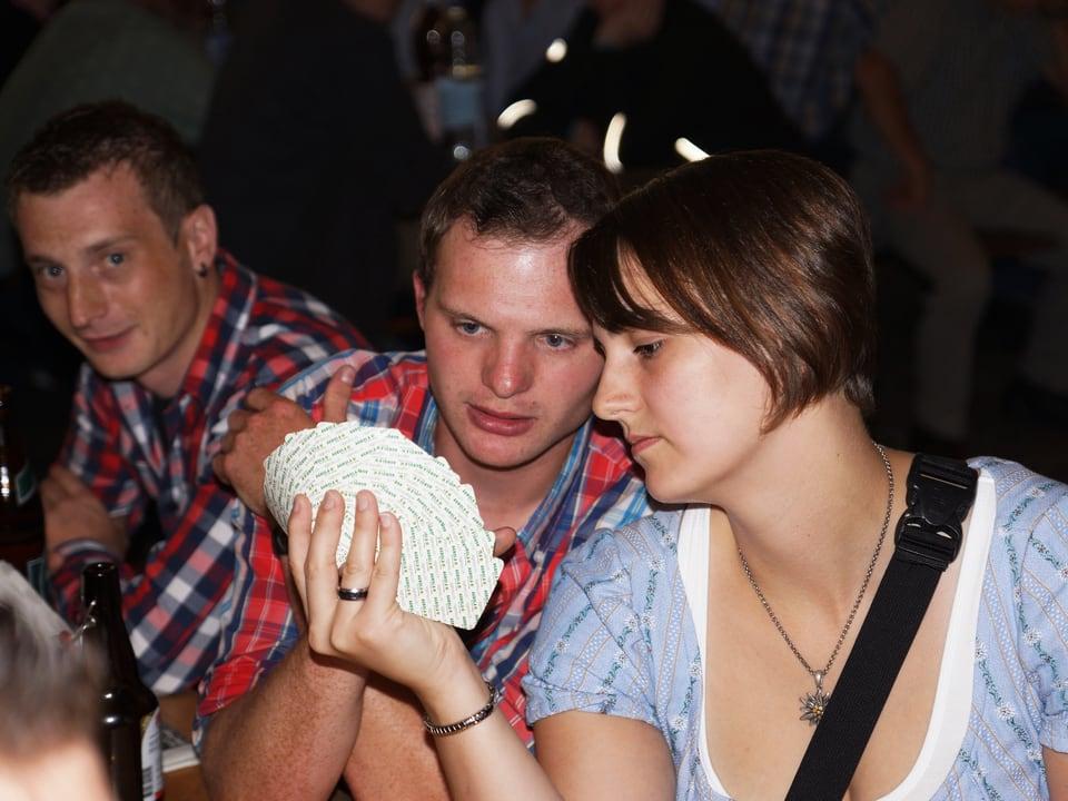Eine junge Frau zeigt ihrem Tischnachbarn, welche Spielkarten sie in den Händen hat.